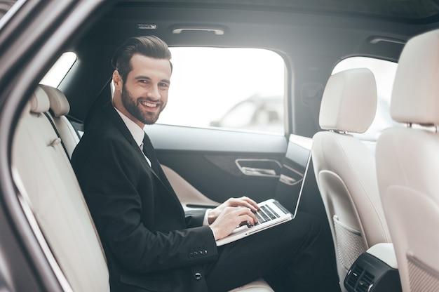 Ótimas soluções todos os dias. jovem empresário confiante trabalhando em seu laptop e olhando para a câmera enquanto está sentado no carro