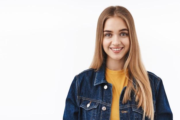 Otimista e feliz garota loira legal em uma jaqueta jeans sobre uma camiseta, olhando para a câmera, sorrindo sincero, expressando atitude amigável positiva
