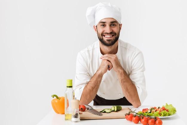 Otimista satisfeito positivo jovem chef feliz em uniforme cozinhando com legumes frescos.