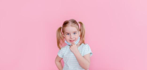 Otimista, sorridente menina feliz tirando a máscara médica do rosto em um espaço rosa, mostrando o fim da pandemia. copyspace.