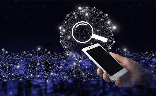 Otimização de mecanismos de pesquisa de tecnologia de pesquisa de dados. mão segure smartphone branco com sinal de dados de pesquisa de holograma digital no fundo desfocado escuro da cidade. ícone de pesquisa de dados do navegador de internet.
