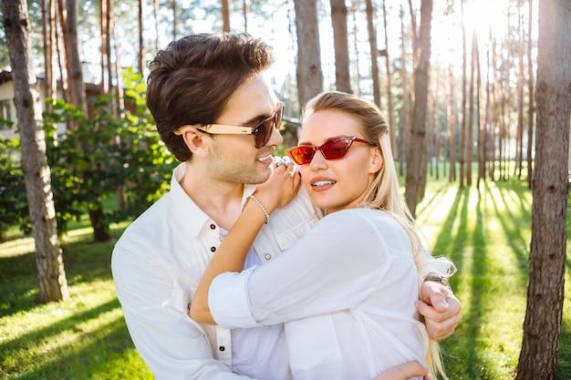 Ótimo dia. mulher agradável e agradável segurando a mão do marido enquanto aproveita o tempo ao ar livre