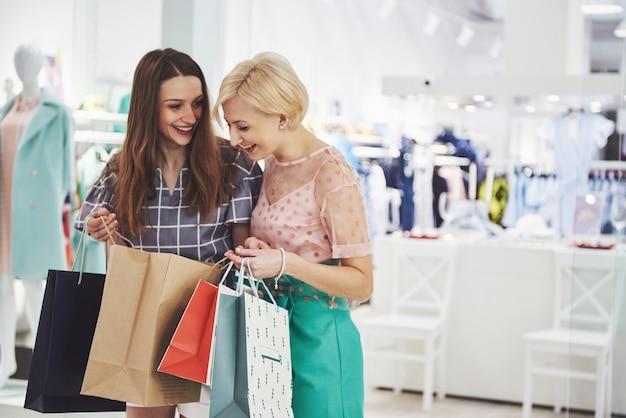 Ótimo dia para fazer compras. duas lindas mulheres olham para a bolsa e se gabam do que compraram.