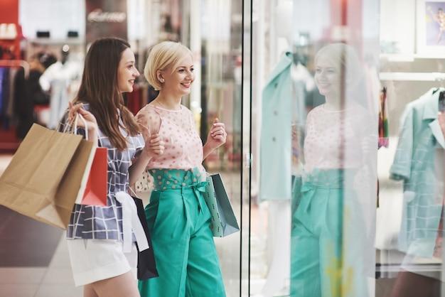Ótimo dia para fazer compras. duas mulheres bonitas com sacos de compras, olhando um ao outro com um sorriso enquanto caminhava na loja de roupas