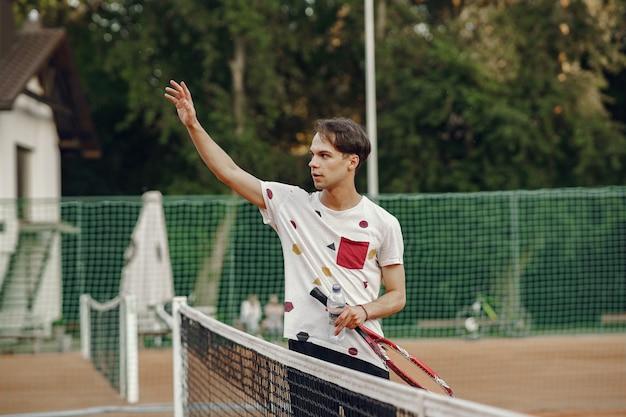 Ótimo dia para jogar! jovem alegre em t-shirt. cara segurando a bola e a raquete de tênis.