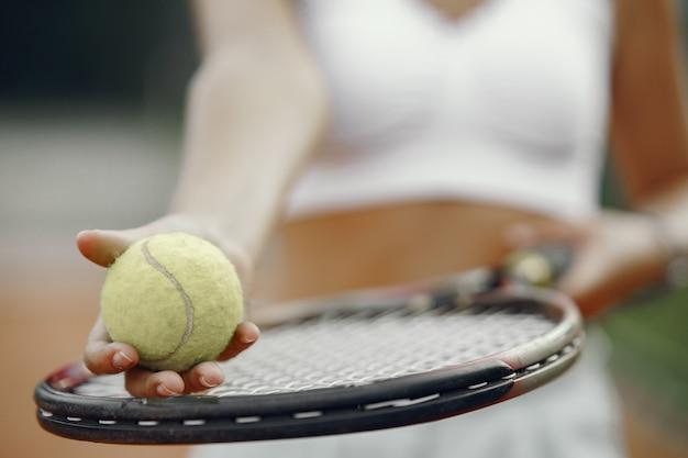 Ótimo dia para jogar! jovem alegre em t-shirt. mulher segurando a bola e a raquete de tênis.