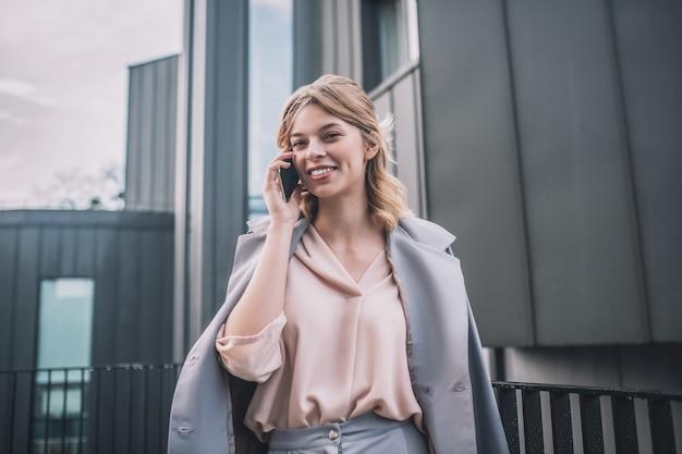 Ótimo humor. jovem alegre e sorridente com uma jaqueta cinza se comunicando em um smartphone em pé à tarde ao ar livre perto do escritório