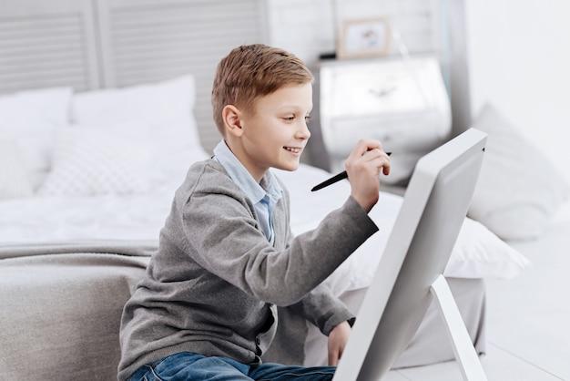 Ótimo humor. menino feliz e encantado olhando para a tela e sorrindo enquanto faz um desenho digital