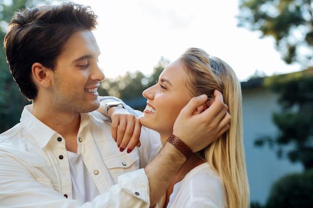 Ótimo humor. mulher alegre e simpática sorrindo enquanto olha para o rosto do marido