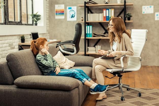 Ótimo humor. mulher positivamente encantada, sentada na cadeira enquanto falava com seu jovem paciente