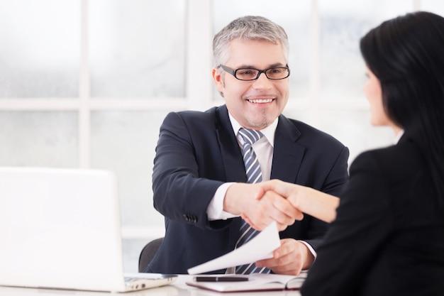 Ótimo negócio! dois executivos apertando a mão e sorrindo, sentados frente a frente à mesa