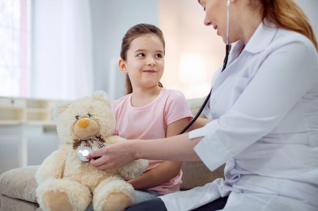 Ótimo paciente. menina bonita olhando para a médica sentada ao lado dela e tratando do urso de pelúcia