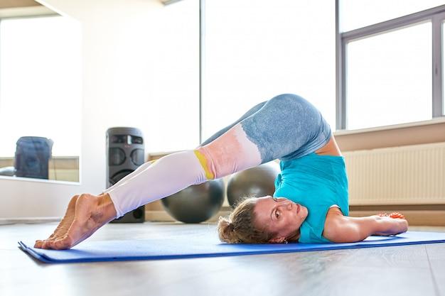 Ótimo progresso. jovem mulher bonita no sportswear fazendo alongamento na frente da janela no ginásio