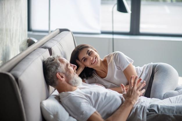 Ótimo relacionamento. homem adulto barbudo contando mulher sorridente e atenciosa ouvindo deitada na cama em casa à tarde