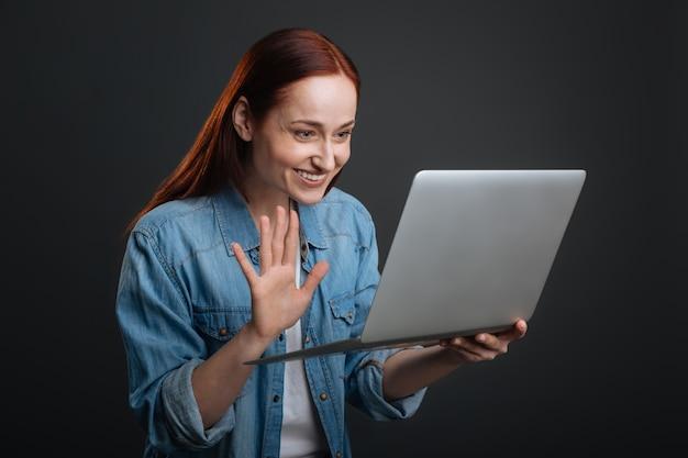 Ótimo ver você de novo. senhora animada e comprometida encantadora fazendo uma videochamada e curtindo uma conversa enquanto usa seu laptop