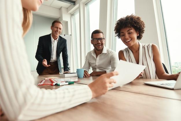 Ótimos resultados grupo de jovens empresários olhando para documentos e sorrindo enquanto estão sentados