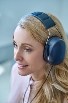 Otorrinolaringologia. rosto de mulher simpática e sorridente com grandes fones de ouvido testando sua audição, experimentando novas sensações