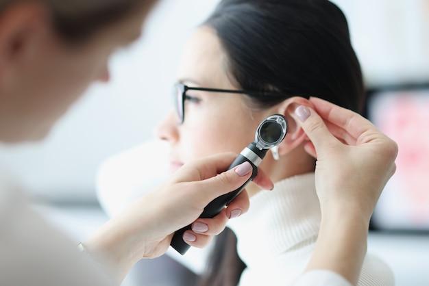 Otorrinolaringologista examina a orelha do paciente com um otoscópio