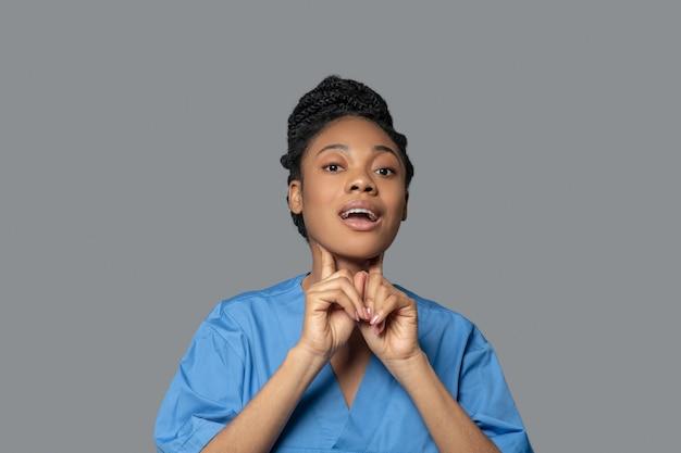 Otorrinolaringologista. foto de um jovem médico de pele escura tocando sua garganta