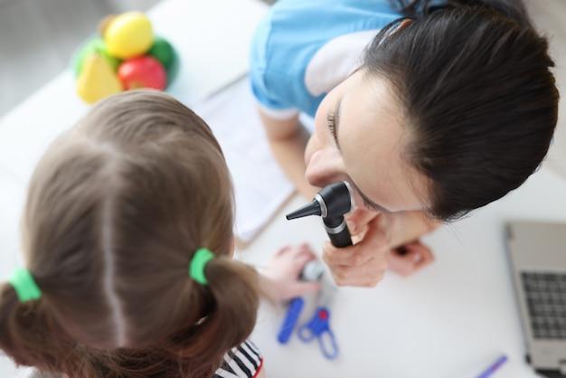 Otorrinolaringologista olha para a orelha da menina com um otoscópio close-up