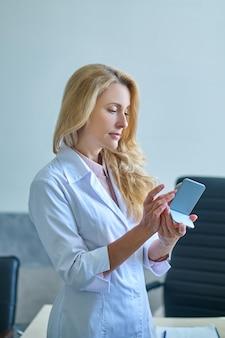 Otorrinolaringologista profissional séria e concentrada, usando um jaleco, examinando um aparelho surdo em suas mãos
