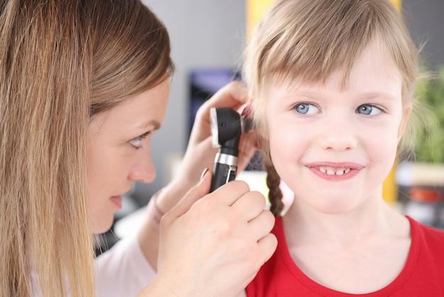 Otorrinolaringologista realiza exame médico de doença do ouvido de menina na infância
