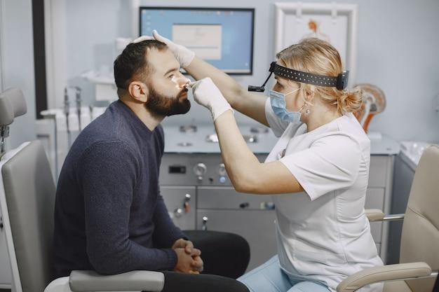 Otorrinolaringologista se preparando para o procedimento de exame médico