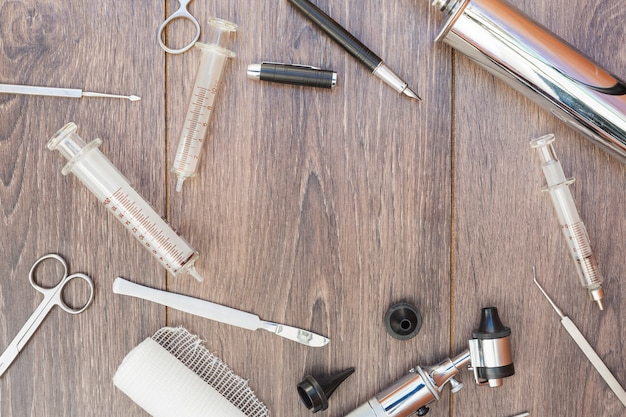 Otoscópio; seringa; instrumentos cirúrgicos; rolo de gaze e caneta-tinteiro preto na mesa de madeira