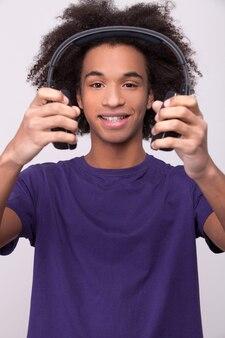 Ouça minha música favorita! adolescente africano alegre segurando fones de ouvido e sorrindo para a câmera