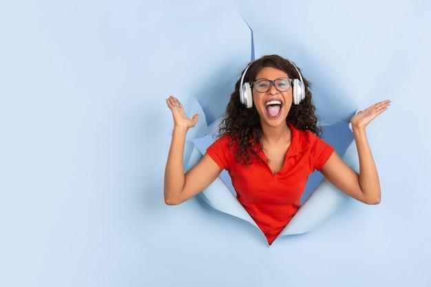 Ouça música, chocado. mulher afro-americana alegre em fundo de papel azul rasgado, emocional, expressivo. rompendo, descoberta. conceito de emoções humanas, expressão facial, vendas, anúncio.