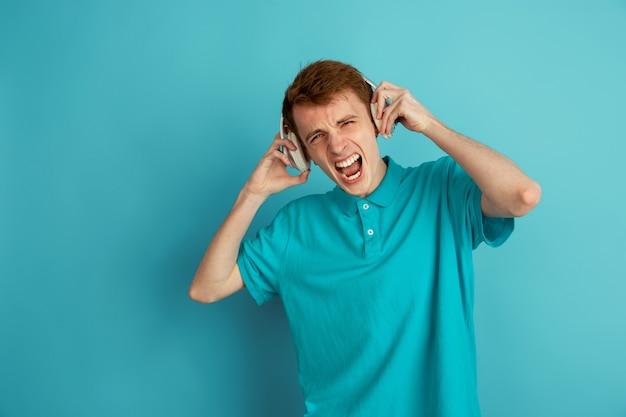 Ouça música, louco. retrato moderno de jovem caucasiano isolado na parede azul, monocromático. lindo modelo masculino. conceito de emoções humanas, expressão facial, vendas, anúncio, moda.