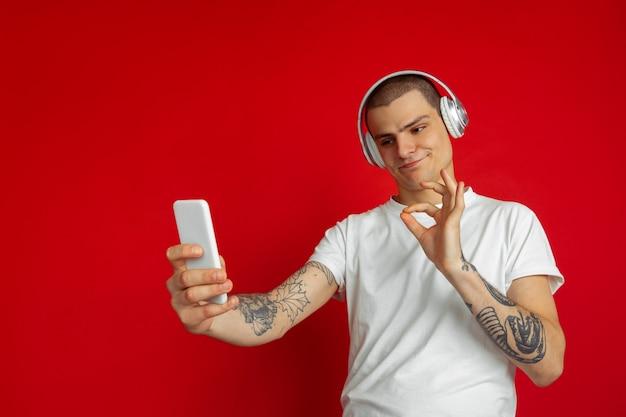 Ouça música, selfie, vlog, tocando. retrato de jovem caucasiano isolado na parede vermelha. lindo modelo masculino. conceito de emoções humanas, expressão facial, vendas, anúncio, tecnologias.
