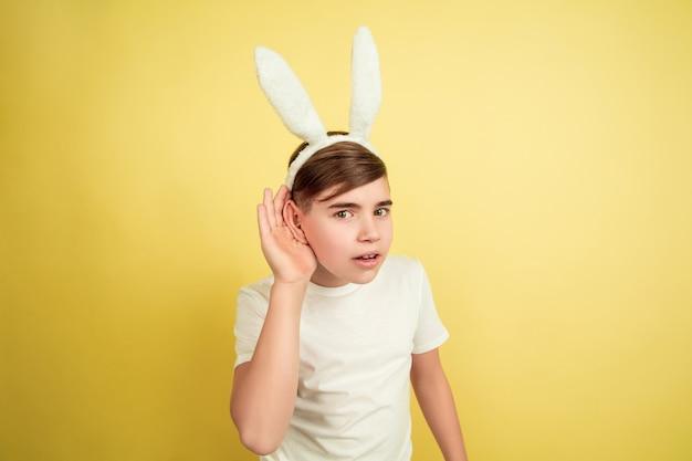 Ouça o segredo. menino caucasiano como um coelhinho da páscoa em fundo amarelo do estúdio. saudações de páscoa feliz. lindo modelo masculino. conceito de emoções humanas, expressão facial, feriados. copyspace.