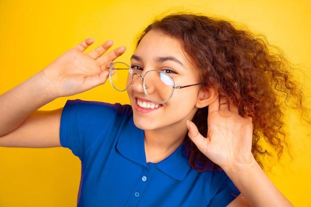 Ouça o segredo. retrato de menina adolescente caucasiano em fundo amarelo do estúdio. linda modelo feminino encaracolado na camisa. conceito de emoções humanas, expressão facial, vendas, anúncio, educação. copyspace.