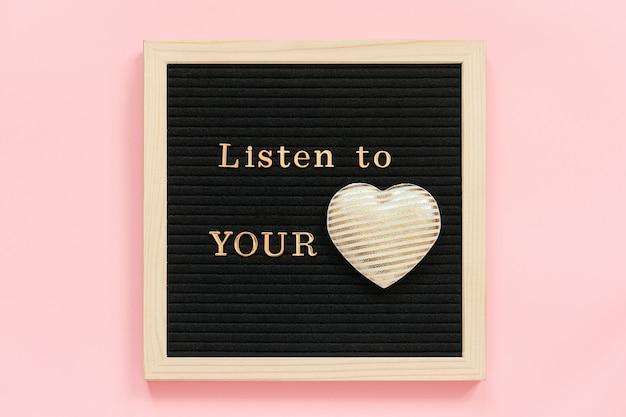 Ouça o seu coração. citação motivacional em letras douradas e coração de têxteis decorativos no quadro de letra preto na parede rosa