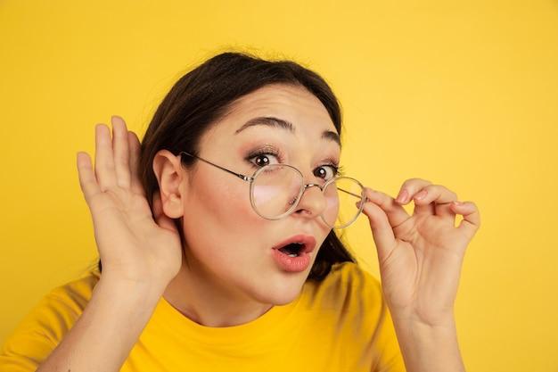 Ouça os segredos. retrato da mulher caucasiana isolado na parede amarela. bela modelo moreno feminino em estilo casual. conceito de emoções humanas, expressão facial, vendas, anúncio, copyspace.