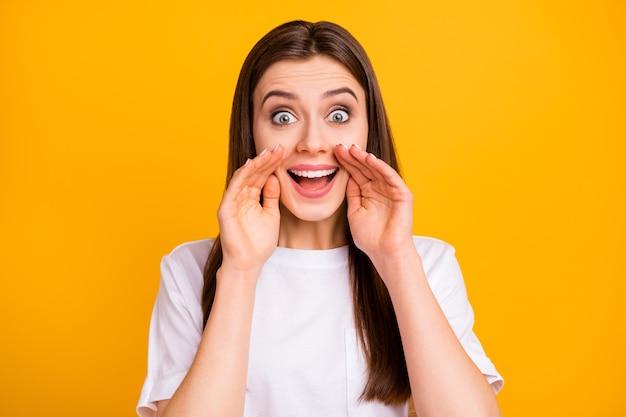 Ouça todo mundo! foto de uma senhora louca engraçada tagarela penteado comprido dizer contar notícias braços perto da boca gossip girl vestir camiseta branca casual isolada parede de cor amarela vívida