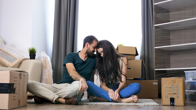 Oung casal se mudando para a nova casa. sentado no chão e relaxando após desfazer as malas
