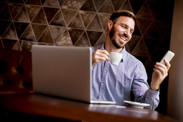 Oung homem sentado em cafés, bebendo café e olhando com um sorriso em um telefone móvel