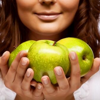 Oung menina com três maçãs verdes frescas