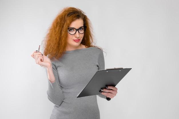 Oung menina de óculos tem uma caneta e um caderno nas mãos