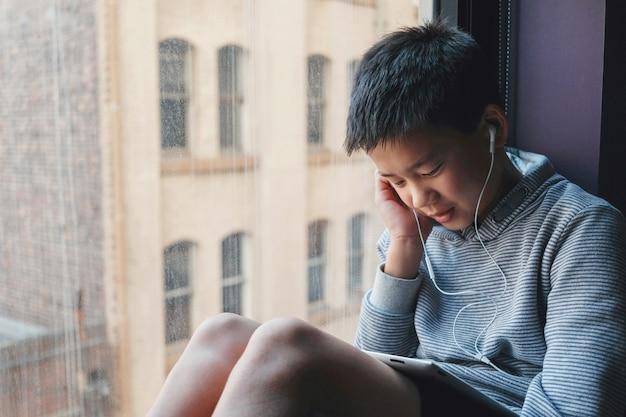 Oung misturado menino pré-adolescente asiático usando tablet digital em casa
