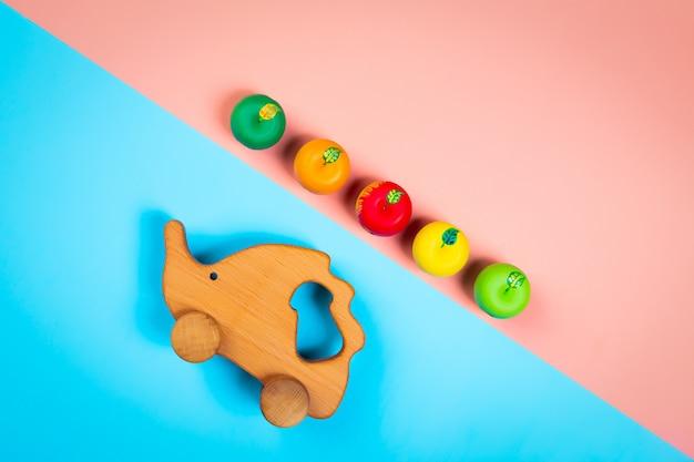 Ouriço de brinquedos de madeira com maçãs coloridas em um fundo geométrico vibrante multicolorido isolado