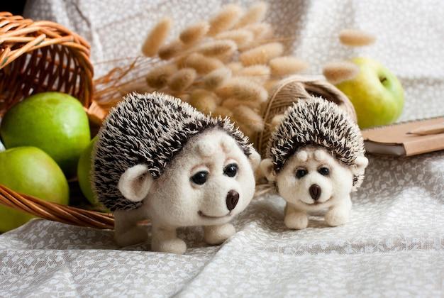 Ouriços fofos de feltro agulhado com fundo de grama seca, maçãs verdes e cesta de vime