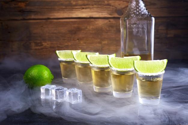 Ouro de tequila mexicana em copos curtos com sal, fatias de limão e gelo em uma mesa de madeira. fumaça.