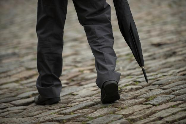 Ouro preto, minas gerais, brasil - 2 de fevereiro de 2016: homem segurando um guarda-chuva andando pela encosta