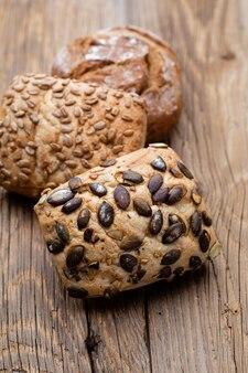 Ouro rústicos pães com crosta de pão e pãezinhos na mesa de madeira. natureza morta capturada da vista de cima, plana. Foto Premium