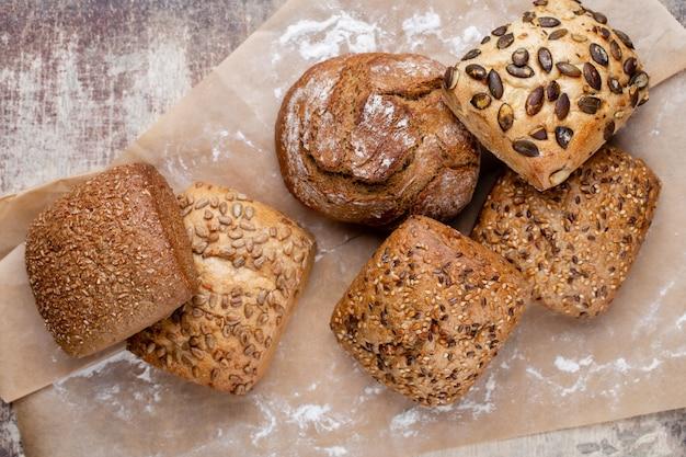 Ouro rústicos pães com crosta de pão e pãezinhos na superfície de madeira. natureza morta capturada da vista de cima, plana.