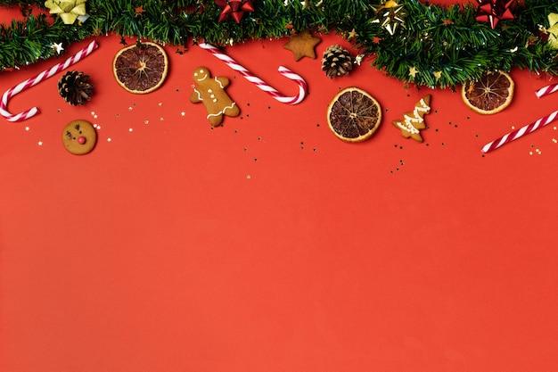 Ouropel de natal, pão de mel, cortador de biscoitos, pirulito, laranja seca, enfeites e pinha no vermelho