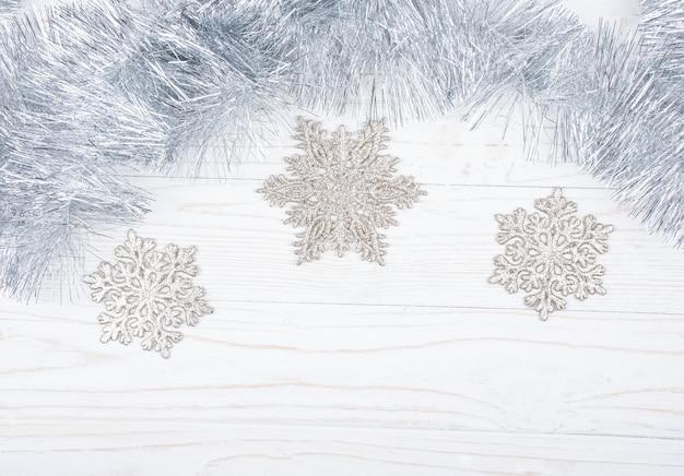 Ouropel de prata e flocos de neve em um fundo de madeira